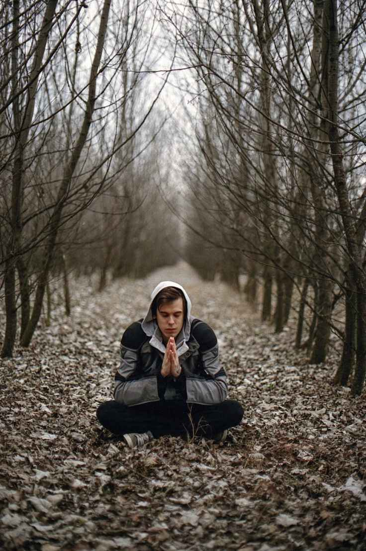 man wearing gray black zip hoodie jacket praying in between black tree during daytime