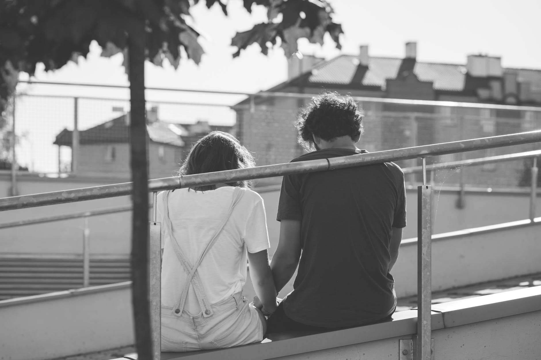 grayscale photo of man and woman sitting on inclined road