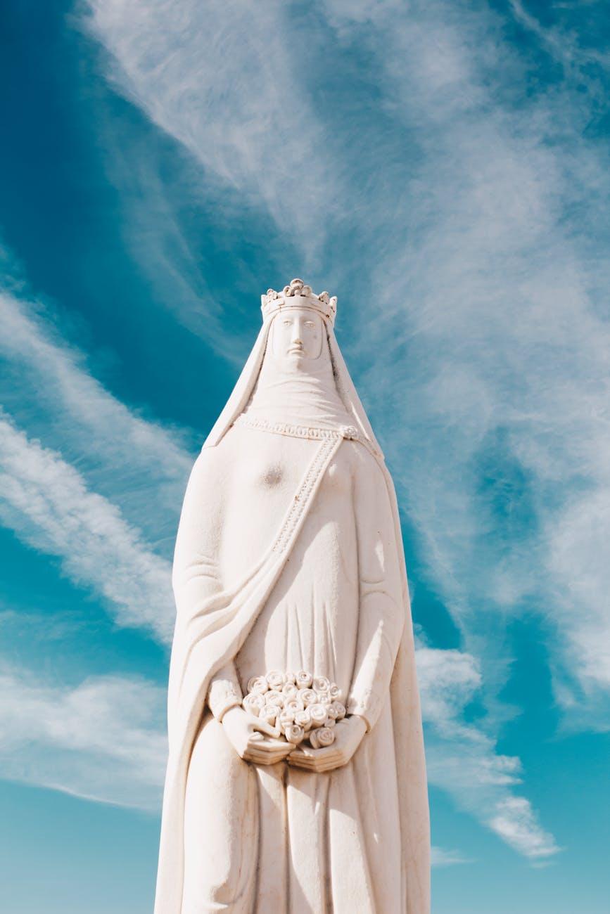 woman concrete statue under clear sky