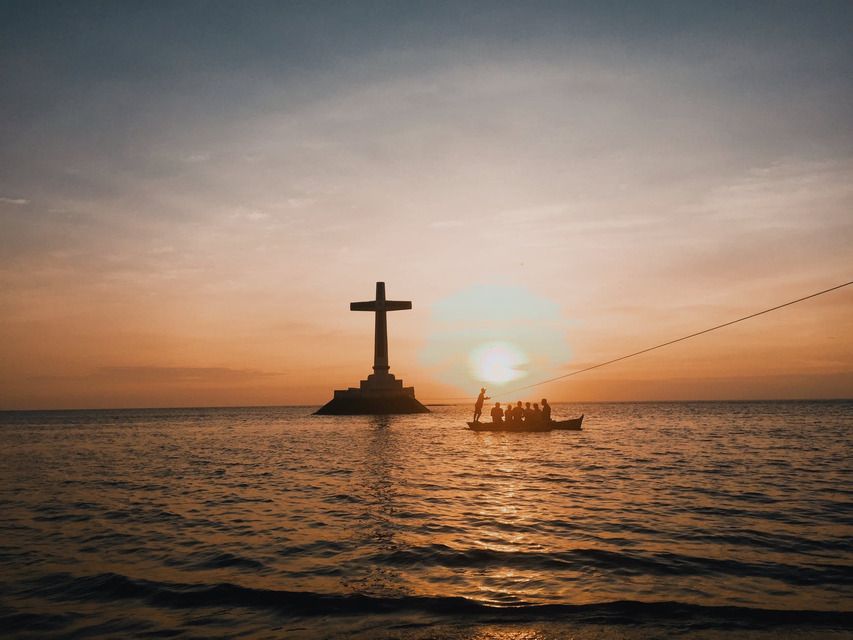 photo of cross in an ocean during dawn