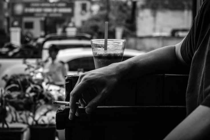 grayscale photo of person resting his arm