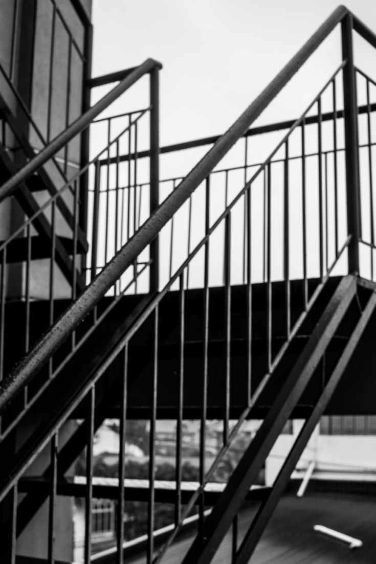 greyscale photo of metal staircase